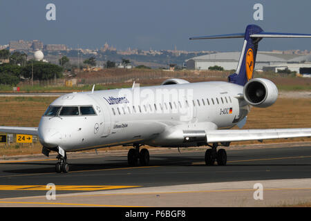 Lufthansa CityLine Bombardier CRJ900 regional jet airliner taxiing for departure from Malta. Air travel and tourism in the EU. - Stock Image