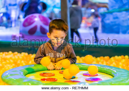 Kownaty, Poland - January 6, 2019: Young boy looking at plastic balls on a air blowing machine on a playground in the Majaland indoor amusement park. - Stock Image