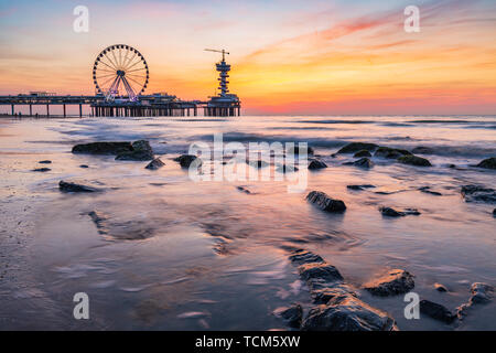 Colorful sunset on coastline, beach, pier and ferris wheel, Scheveningen, the Hague. - Stock Image