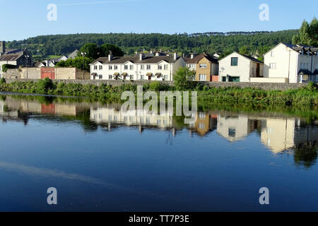 The image of colorful riverside houses reflecting in the calm river. - Stock Image