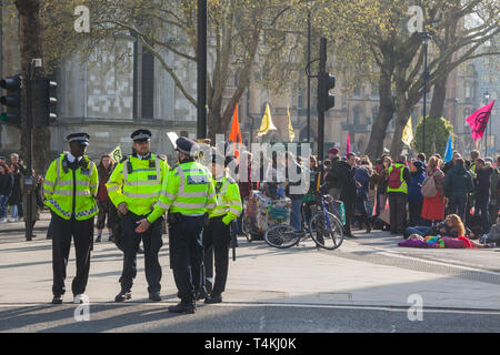 Metrolpolitan Police stand by on Parliament Square, Westminster for the Extinction Rebellion demonstration with protestors and banners behind - Stock Image