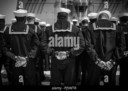 180825-N-UX013-1076 U.S. 5TH FLEET AREA OF OPERATIONS (Aug. 25, 2018) Sailors stand at parade rest during a memorial ceremony at sea for Ensign Sarah Mitchell aboard the guided-missile destroyer USS Jason Dunham (DDG 109). Dunham is deployed to the U.S. 5th Fleet area of operations in support of naval operations to ensure maritime stability and security in the Central Region, connecting the Mediterranean and the Pacific through the western Indian Ocean and three strategic choke points. (U.S. Navy photo by Mass Communication Specialist 3rd Class Jonathan Clay/Released) - Stock Image
