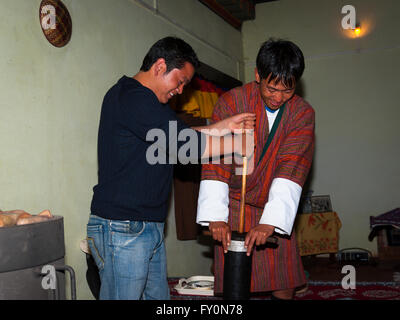 Two men making salted butter tea with a traditional churn in Kurjey, Bumthang, Bhutan. - Stock Image