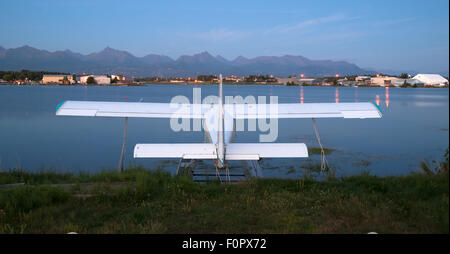 A plane sits waiting for the next chance to be of service as darkness falls on Anchorage - Stock Image