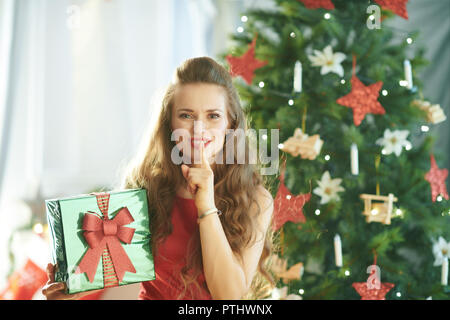 happy young woman in red dress with green Christmas present box showing shh gesture near Christmas tree - Stock Image