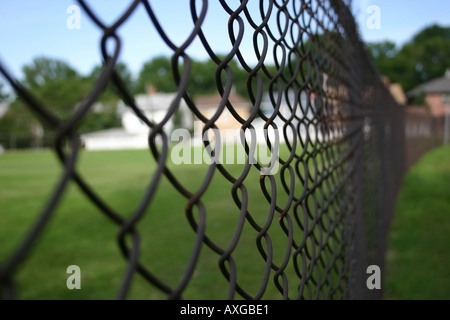 A slightly rusted fence runs off into the background. - Stock Image