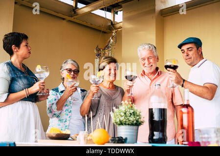 Cheerful group of mixed ages senior adult friends enjoy and celebrate together with big glass and cocktails or wine at home - mature friends during pa - Stock Image