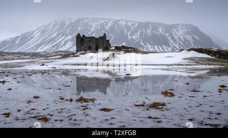 Old farmhouse in front of a mountain, andscape along the southern coast of Iceland at wintertime - Stock Image