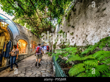 Tourists window shop on a picturesque, narrow alley covered with ivy, shaded from the sun in Positano Italy on the Amalfi Coast of the Mediterranean - Stock Image