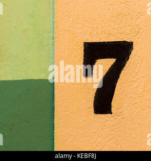 The number seven painted on a coulourful wall of yellow and green patches. - Stock Image