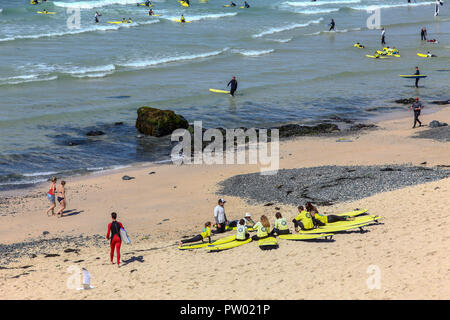 Surfers being instructed at a surf school on Porthmeor beach, St. Ives, Cornwall, England, UK - Stock Image