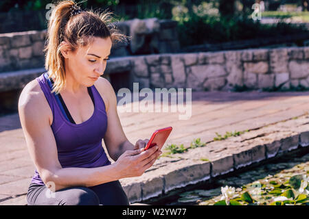 young sporty woman sitting writing at the phone at park, technology at sports and healthy lifestyle - Stock Image