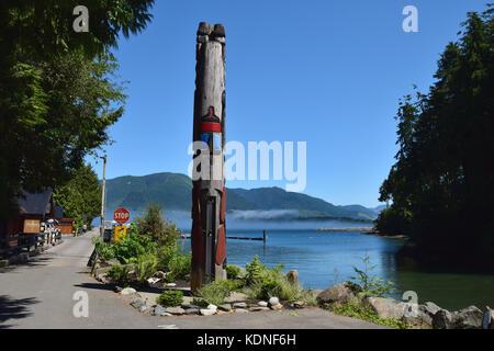 Totem pole rises over the harbor mist - Port Renfrew, Vancouver Island,  BC, Canada - Stock Image