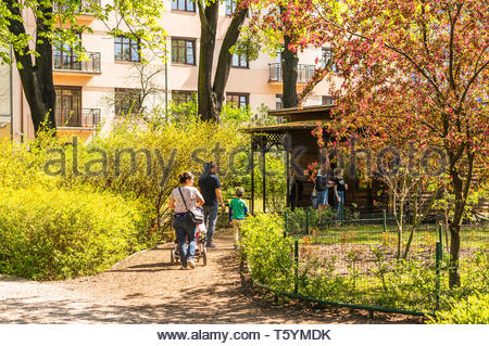 Poznan, Poland - April 18, 2019: Woman holding buggy and man with boy walking on a footpath along trees leading to a small hut with animals in the old - Stock Image