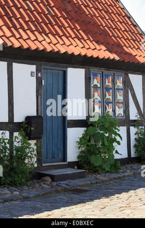 Quaint old timbered single-story residential house front door and window. Ebeltoft, Jutland, Denmark, Scandinavia - Stock Image