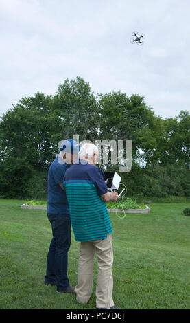 Two men operating a dji Phantom Quadcopter Drone unmanned aerial vehicle in flight. - Stock Image