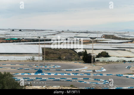 Invernaderos, greenhouses, hothouses for soil free crops with motorcycle race track in the foreground in Murcia, - Stock Image