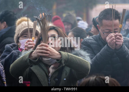 People with incenses in Yonghe Temple also called Lama Temple of the Gelug school of Tibetan Buddhism in Dongcheng District, Beijing, China - Stock Image