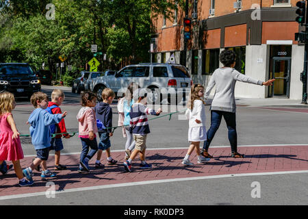 Adult, possibly teacher leading young children across street with rope. - Stock Image