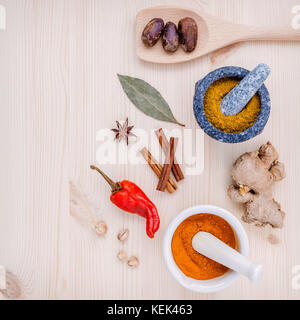 Dried herbs and spices nutmeg,star anise ,cinnamon stick ,ginger ,bay leaves and chili on wooden table. Top view - Stock Image