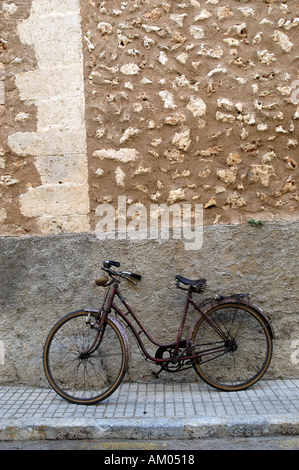 A red bike leaning against an old, rock wall. - Stock Image