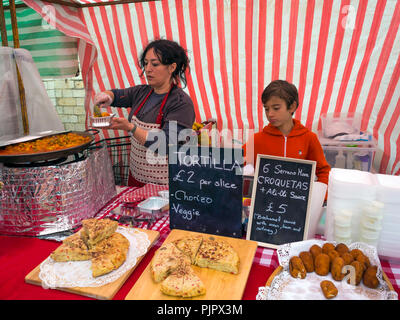 A Spanish woman stall holder at a UK farmer's market serving a portion of steaming hot Paella - Stock Image
