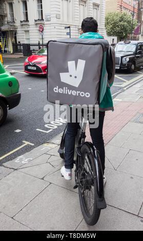 Male Deliveroo cyclist on Southampton Row, Bloomsbury, London, UK - Stock Image