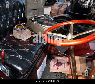 Close-up of the interior of a veteran car, showing an old wind-up gramophone, with driving goggles and a hat, at the Regents Street Motor Show 2018 - Stock Image