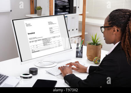 Close-up Of A Businesswoman's Hand Checking Invoice On Laptop Over White Desk - Stock Image