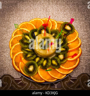sliced oranges with kiwi on a plate,fresh fruit,festive table,dessert on the plate - Stock Image
