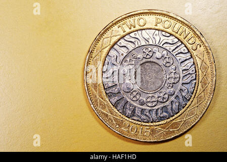 Two pound English currency coin in a macro close-up on a rich luxurious golden background. Copyspace area for finance, - Stock Image