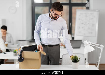 sad fired male office worker with personal stuff - Stock Image