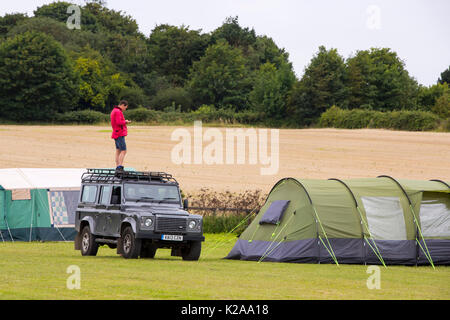 A man trying to get a phone signal on the roof of his Landrover on a campsite in Cley on the North Norfolk coast, UK. - Stock Image