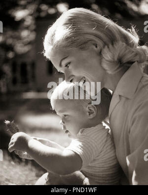 1960s SMILING BLOND MOTHER HOLDING CHILD WITH LEAF  - j11262 CLE003 HARS JUVENILE BLOND SECURITY YOUNG ADULT SAFETY STRONG SONS PLEASED FAMILIES JOY PARENTING FEMALES HEALTHINESS HOME LIFE COPY SPACE CARING MALES B&W TODDLERS DREAMS HAPPINESS HEAD AND SHOULDERS LEAF PROTECTION LOVING SMILES JOYFUL MOTHERHOOD BABY BOY PERSONAL ATTACHMENT AFFECTION EMOTION GROWTH JUVENILES MOMS TOGETHERNESS YOUNG ADULT WOMAN BLACK AND WHITE CAUCASIAN ETHNICITY OLD FASHIONED - Stock Image