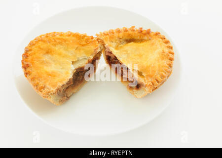 Savoury meat takeaway pie with a beef filling cut in half on a white plate - Stock Image