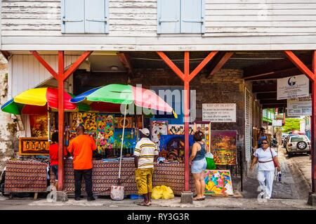 Dominica, Capital Roseau, scene of everyday life, art display and craftwork backed by a creole house, in the city center - Stock Image