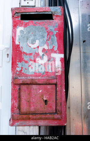 Metal Post box painted red with chipped paint and bare metal showing through. - Stock Image