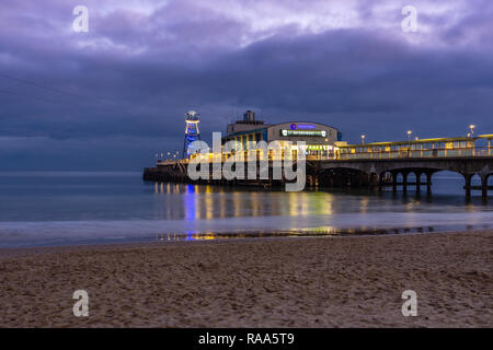 Bournemouth Pier with lights reflected at night / twilight, January 2019, Bournemouth, Dorset, England, UK - Stock Image