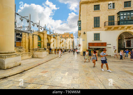 Tourists and local Maltese pass by the Ruins of the Royal Opera House in Valletta, Malta. - Stock Image
