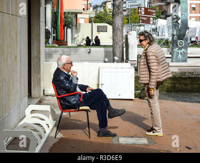 Conversation between old friends in Aulla, Tuscany. Man sits in retro-style red chair. - Stock Image
