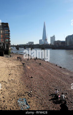 Vertical view of River Thames at low tide, Southwark Bridge, Shard building, people mudlarking near Queenhithe in London EC4 England UK  KATHY DEWITT - Stock Image