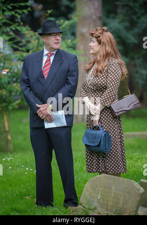 Woodhall Spa 1940s Festival - A couple dressed in 1940s dress waiting in a churchyard waiting for Remnembrance Service - Stock Image