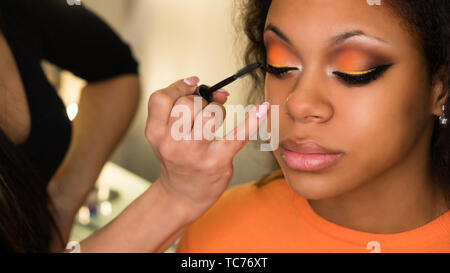 Makeup artist applies mascara to eyelashes of african girl. Evening make-up. Closeup portrait - Stock Image