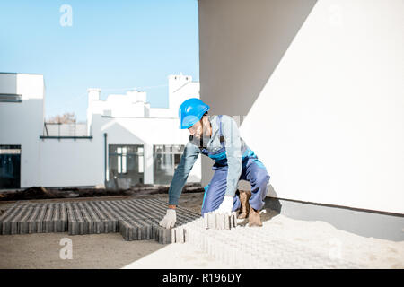 Builder in uniform mounting paving tiles on the construction site with white houses on the background - Stock Image