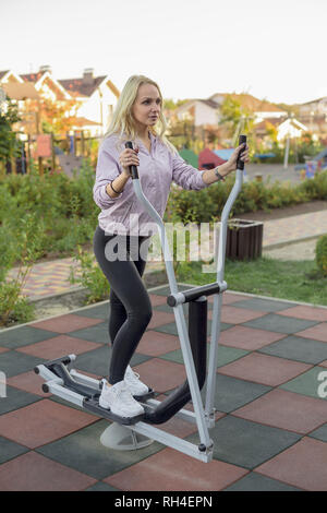 Fit woman using elliptical machine on patio - Stock Image