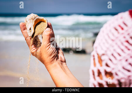 Nature and environment concept with close up of woman hands with shell and sand - travel and holiday summer vacation at the beach - blue sea and waves - Stock Image