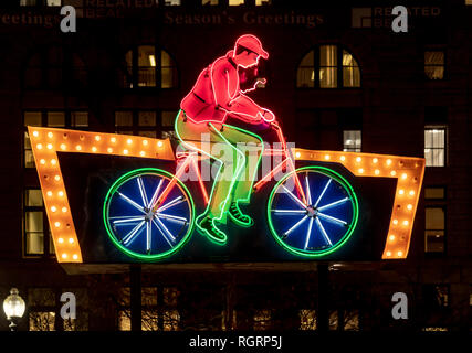 Cycling man animated, illuminated neon sign shot at night time in Boston, preserved together with others on Rose Fitzgerald Kennedy Greenway. - Stock Image