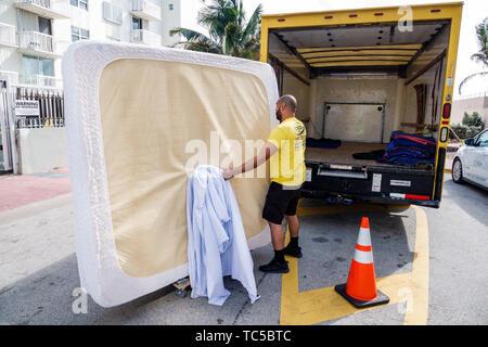 Miami Beach Florida moving van company movers king size mattress Hispanic man employee working job - Stock Image