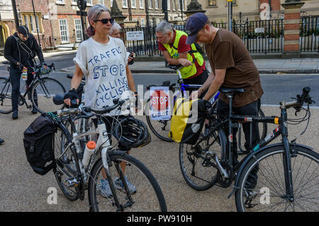 London, UK. 13th October 2018. Cyclists meet for a  funeral procession of behind a horse-drawn hearse to highlight the failure of governments from all the major parties to take comprehensive action on safer cycling. Stop Killing Cyclists call for £3 billion a year to be invested in a national protected cycling network and for urgent action to reduce the toxic air pollution from diesel and petrol vehicles which kills tens of thousands of people every year, and disables hundreds of thousands. The several hundred protesters staged a ten-minute die-in outside Parliament before moving off to a rall - Stock Image