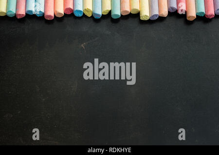 Group of multicolored chalks on black chalkboard with copyspace. - Stock Image